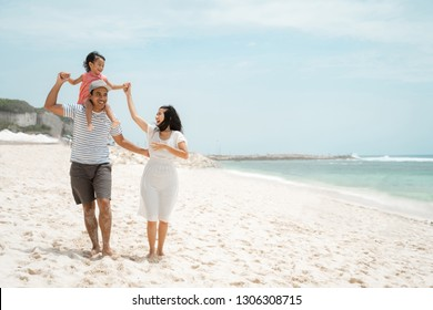 young father carrying daughter on the shoulder when enjoy the beach with mother at middle day