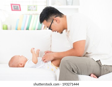 Young father changing diaper and clothes for baby boy. Asian family lifestyle at home.