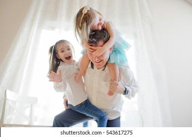 Der junge Vater verbringt fröhlich Zeit mit den kleinen Töchtern. Jüngere Mädchen sitzt am Vater auf den Schultern und schließt seine Augen mit den Händen. Ein anderer hat sich auf dem Bein eines Vaters niedergelassen.