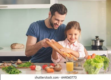 Young father and daughter cooking meal together