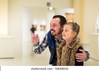 young father and daughter exploring expositions in museum halls