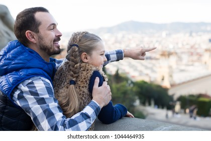 young father and daughter pointing at sight during sightseeing tour outdoors