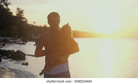 Young father and daughter spending happy time at the beach during amazing sunset