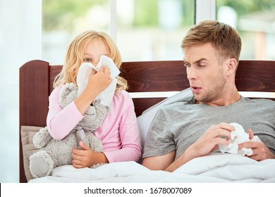 Young father and daughter suffering from flu or cold, having runny noses while resting in bed together at home. Virus disease. Coronavirus concept. Sick family at home. Health concept