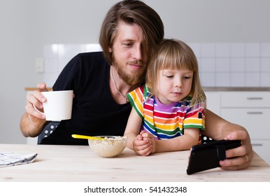 young father drinking morning coffee and watching mobile phone together with kid on kitchen