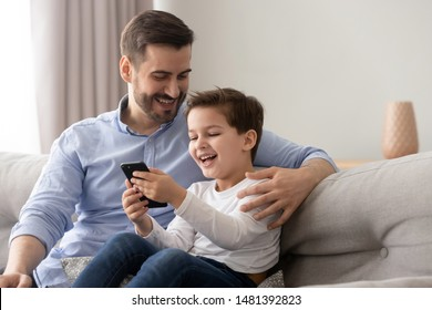 Young father embraces little son family sitting on couch at home using smart phone feels happy cheerful laughing on pranks online funny videos, parental control and modern tech everyday usage concept