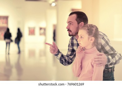Young father and girl exploring paintings in halls of museum