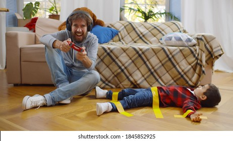 Young father in headphones playing video game with console on disobedient son tied with duct tape on floor. Dad looking after kid alone in living room
