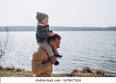Junge Vater und ihr Sohn amüsieren sich im Frühjahr am Seeufer in der Natur im Park.