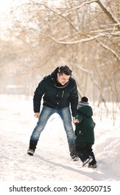 Young father and his child having fun in winter park on a bright day hugging each other and smiling