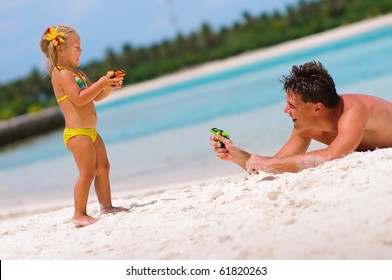 young father and his cute daughter playing with water guns on exotic beach