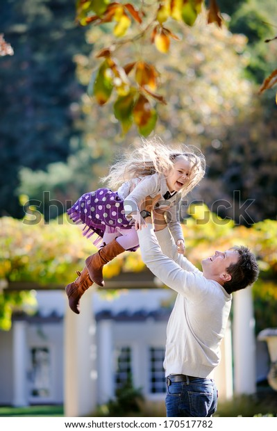 Young father and his cute little daughter have a fun in beautiful nature background