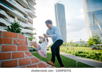 Young father and his daughter playing in the city park near the skycrapers. Sunny summer day. Happy family