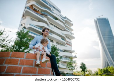 Young father and his daughter sitting on the brick sculpture in the city park near the modern skycrapers. Sunny summer day. Happy family