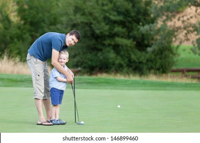 young father and his happy smiling son playing golf together