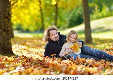 Young father and his little daughter sitting on yellow maple leaves on beautiful sunny autumn day