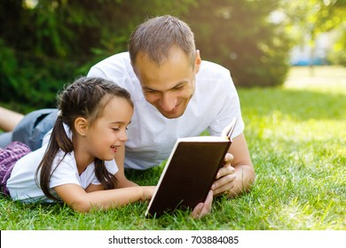 a young father with his little daughter reads the Bible