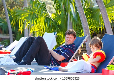 Young father and his little son resting near swimming pool. Man and little preschool kid boy in swim floaties making family vacations on the beach with palms.