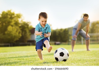 Young father with his little son playing football on football pitch
