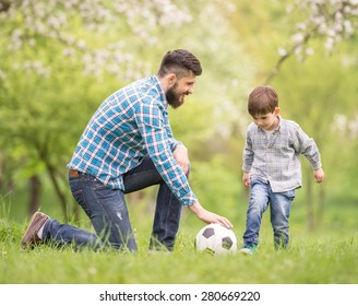Young father with his little son having fun on football pitch.