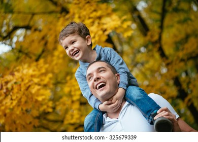 Young father and his little son enjoy outdoors in a park. Father holding his son on the shoulders. Selective focus on kid face.
