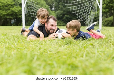 A Young father with his little son playing football on football pitch
