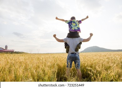 young father with his little son walking in the wheat field at sunset in a warm summer day