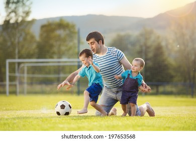 Young father with his little sons playing football on football pitch