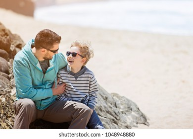young father and his smiling son enjoying time together at the beach, father's day concept, copy space on the right