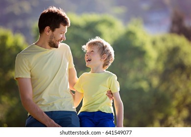 young father and his smiling son in identical clothing sitting, hugging and enjoying time together, father's day celebration