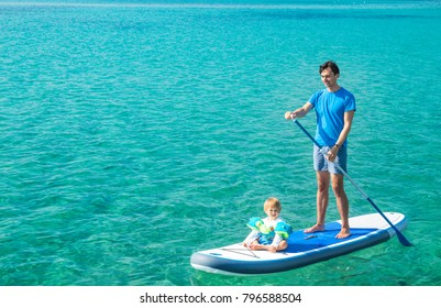 Young Father with His Son on SUP. Dad and Son Concept. Man and Boy Stand Up Paddling. Blue Sea Water. Floating Sup Board. Dad and Son on Summer Vacation Concept. Copy Space.
