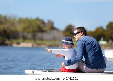young father and his son sitting at the marina dock and spending fun time together; adorable little boy pointing with his finger and showing something to his father