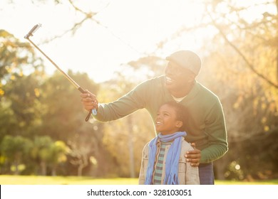 Young father and his son taking selfies on an autumns day