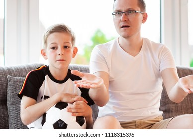 Young father and his son watching world soccer championship with ball on the sofa