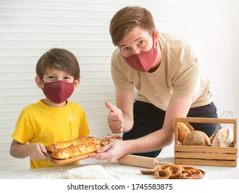 Young father and his son wearing face masks while baking bread at home.Stay at home , Social distancing concept.