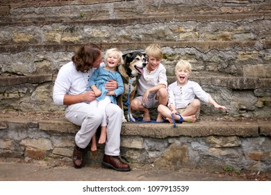 A Young Father and his three happy little children are sitting at a park outside on an old stone staircase with their German Shepherd Dog on a Summer Day.