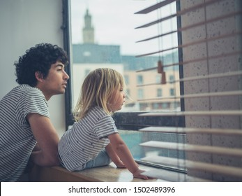 A young father and his toddler are looking out the window of a city apartment
