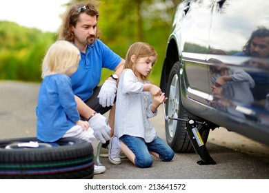 Young father and his two daughters changing a car wheel outdoors on beautiful summer day