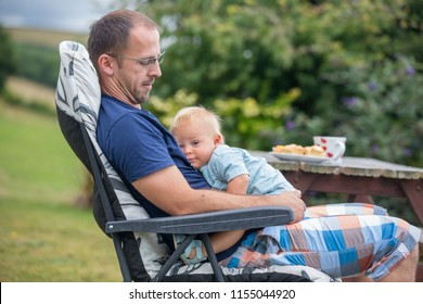 Young father holding his cute baby boy, cuddle him, hugging and kissing, smiling happily, rural outdoor cozy place