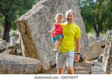 Young father holding his little daughter. Sweet blond little baby girl in beautiful dress with dad in yellow t-shirt. Famous Archaeological Site of Olympia. Peloponnese, Greece. Travel concept