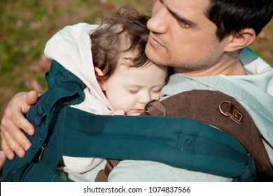 Young father holding a little child in a backpack on a chest.