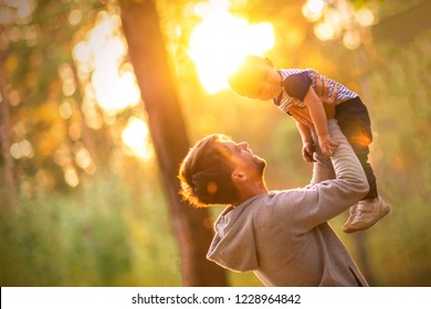 Young father holds his son. Man is having fun with his little baby in a summer park. Happy dad throws up child while playing outdoors