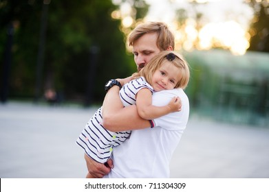 Young father holds the little daughter on hands. Man gently presses to himself the child. Baby put her head on her father's shoulder.