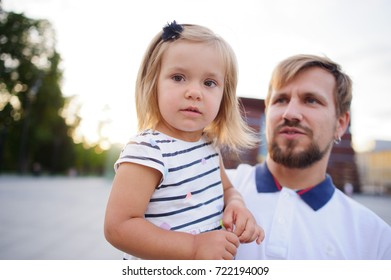 Young father holds the little daughter on hands. Man gently presses to himself the child.