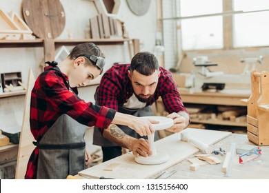 Young father is keen on making DIY wooden toy together with his son on carpentary masterclass in woodworking studio. Dad is helping his son to mark up lines on wooden plank with ruler