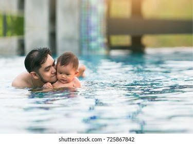 Young father kiss a little son swimming in pool.