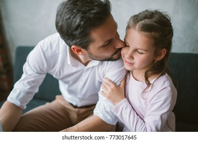 Young father kissing his little daughter and reading book