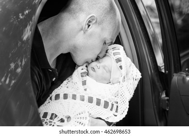 Young father kissing newborn daughter sitting on the back seat of the car.Black and white photography