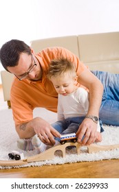 Young father and little baby boy playing together with toy train at home.