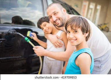 Young father and little boys washing car in summer day